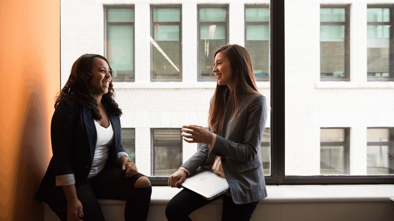 2 happy women talking in office | happiness at work