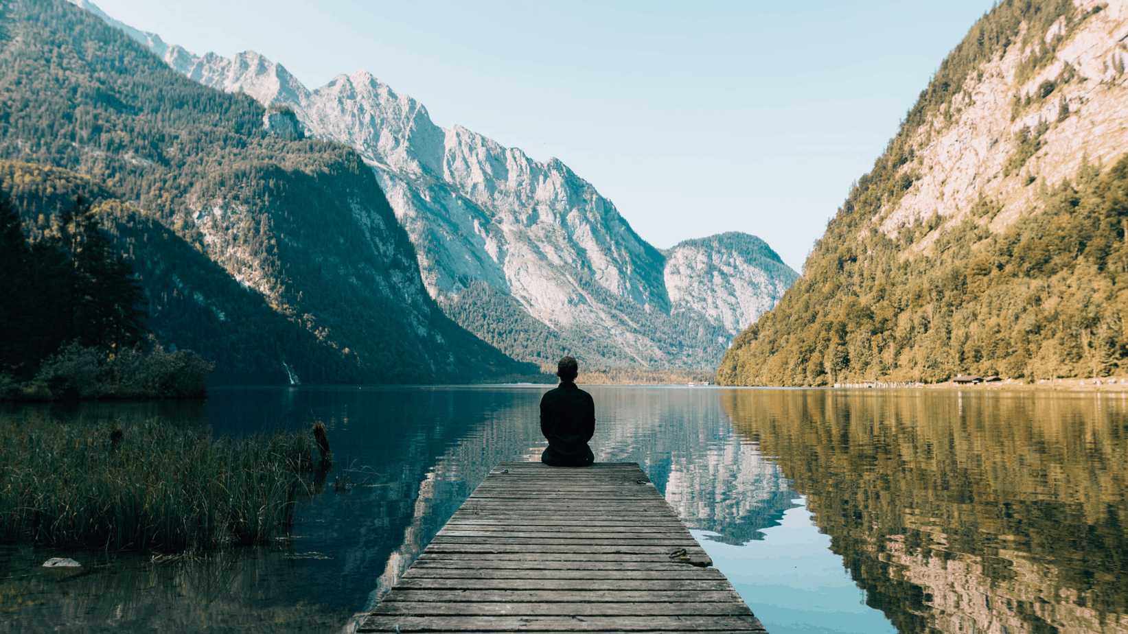 man stting on lake dock with mountains | strategies to take care of your mind + body post-pandemic